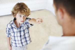 A young boy reprimanding his father at home